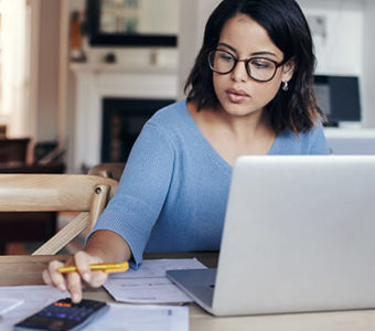 Woman looking at paperwork while working on computer