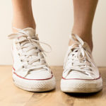 Closeup of person wearing white tennis shoes