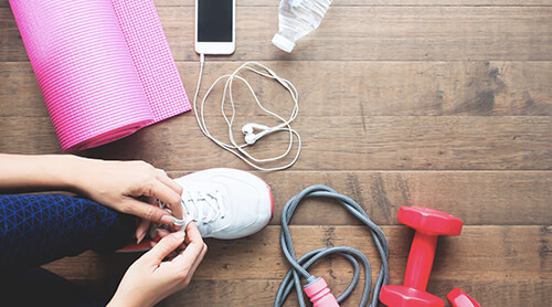 Closeup of person tying their gym shoe next to a yoga mat, weights and a phone with headphones attached