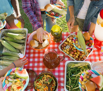 Overhead shot of potluck spread out on table with people around it