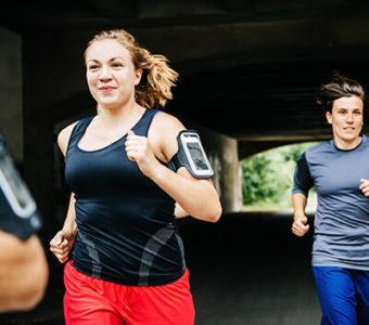 Group running outdoors under bridge