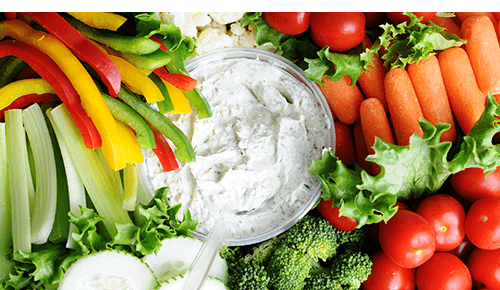 Variety of cut vegetables surrounding a bowl of dip
