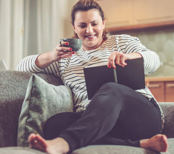 Woman holding a cup of tea while reading a book on a couch