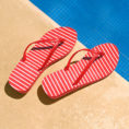 Red and white striped flip flop sandals sitting next to pool