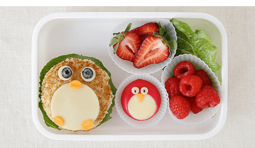 Lunchbox container with a sandwich and snacks decorated to look like animals