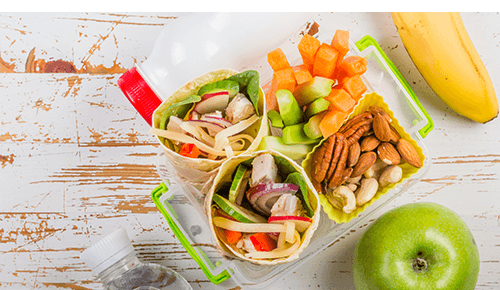 Lunchbox container with a vegetable wrap, cut up raw veggies and nuts