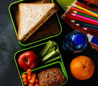 Several lunchbox containers with a variety of healthy food and snacks sitting on top of a chalkboard