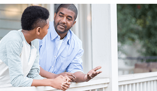 Father talking to teenager on porch of house