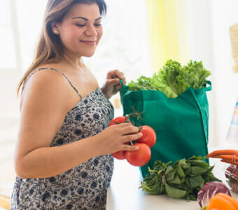 Woman unpacking fruits and vegetables from a shopping bag sitting on a kitchen counter