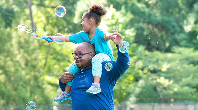 Father with daughter on his shoulders playing with bubbles outside