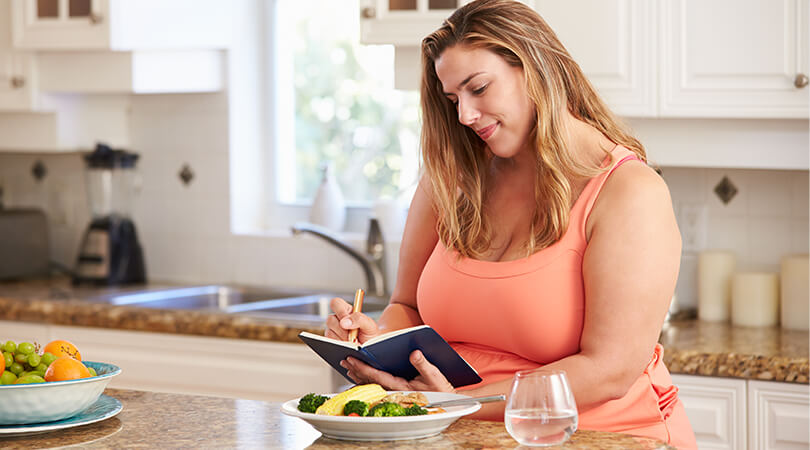 Woman writing in journal at kitchen counter with plate of food near her