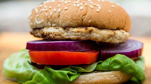Grilled chicken sandwich on wheat bun with lettuce, tomato and onions topping it