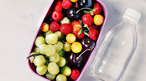 Container with assorted fresh fruit sitting next to a water bottle