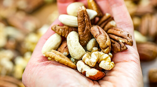 Hand holding a variety of raw nuts