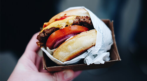 Hand holding a burger in bun topped with cheese, tomato and onion