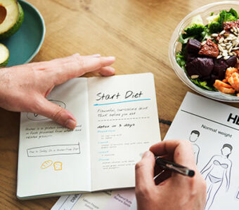 Person writing in diet and workout journal with a salad on the counter next to them