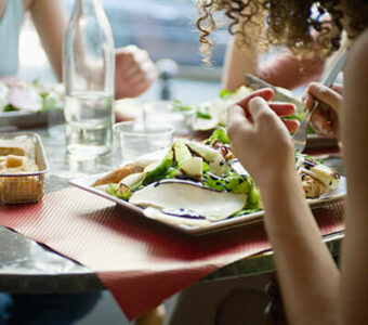 Closeup of a group of people dining together with meals on plates in front of them