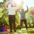 Mother and daughter doing jumping jacks and exercising outside in sun