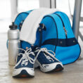 Closeup of gym shoes sitting in front of a gym bag, towel and water bottle