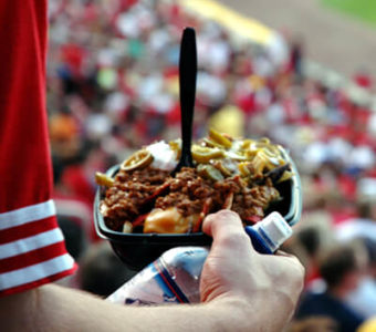 Closeup of person standing in packed sports stadium holding a plate of loaded nachos