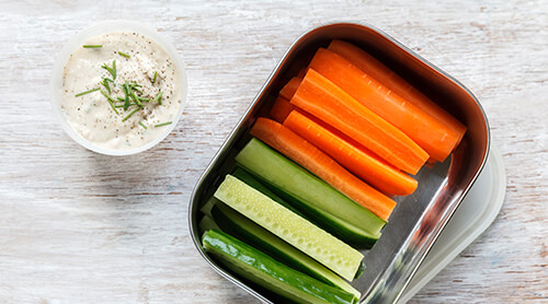 Tin container of cut carrots and celery with a side of dipping sauce