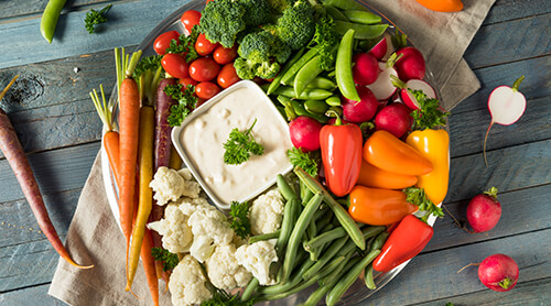 Large plate of cut up fresh vegetables with dipping sauce in the middle of them