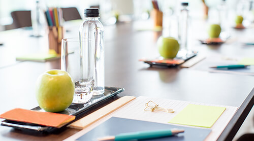 Closeup of apple and water bottles sitting at places around a table for individuals attending a work meeting