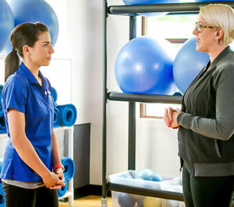 Woman talking to exercise physiologist in gym