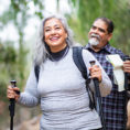 Couple walking on a trail outdoors using walking poles