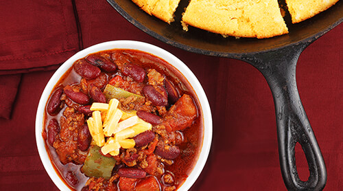 Bowl of chili next to a pan of cornbread