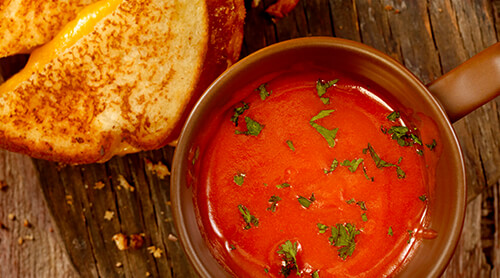 Bowl of tomato soup with slices of grilled cheese sandwich next to it