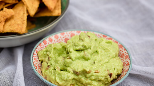 Bowl of guacamole next to a bowl of tortilla chips