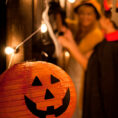 Jack-'o-lantern sitting on table with group in costumes in background
