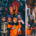 Group of children and adult, all in costume, being greeted at doorway to receive candy for Halloween