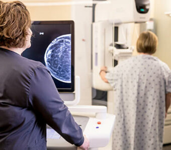 Clinical staff viewing screen as woman in background receives a mammogram