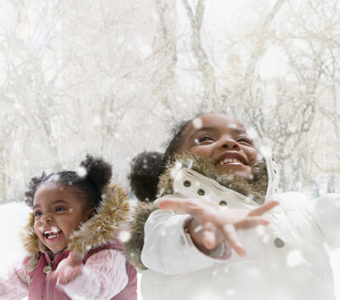 Two children smiling with arms out looking up at the snowflakes falling