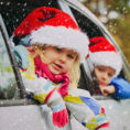 Children wearing Santa hats looking out the windows of a car