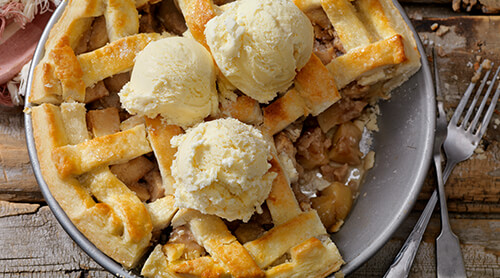 Top view of an apple pie with scoops of vanilla ice cream on top
