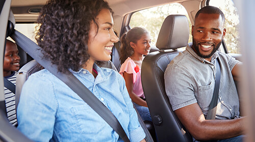 Family in car, parents smiling at each other