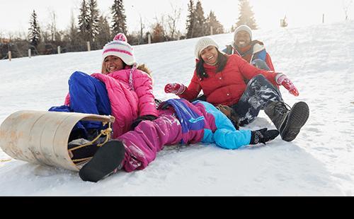 Family sledding on snowy hill