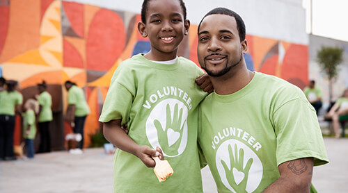 Adult and child wearing matching Volunteer shirts and holding paint brushes in front of wall mural