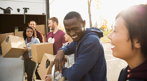 Group of smiling people volunteering and loading boxes into a truck