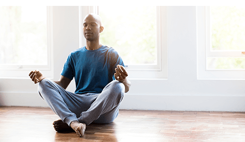Man with eyes closed meditating on the floor