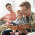 Parents reading a book to a baby
