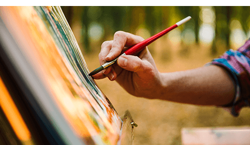 Person painting on canvas outdoors