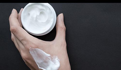 Closeup of a hand holding a jar of face moisturizer