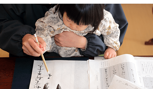 Adult and toddler writing with ink in a notebook