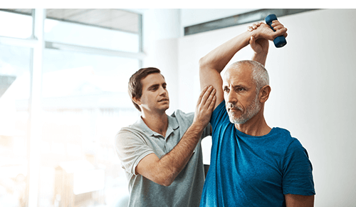 Man exercising with dumbbell with help from a physical therapist
