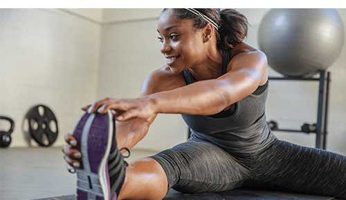 Woman stretching her legs after exercise in gym