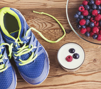 Athletic shoes sitting on ground next to healthy foods
